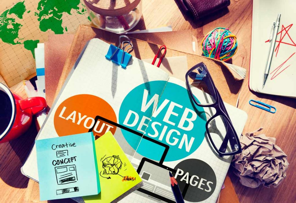 image of a messy desk with web design sketches and layouts